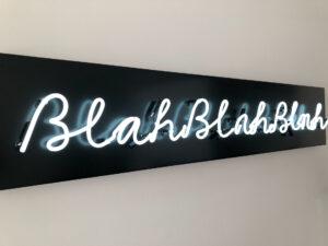 """Neon sign in cursive text that says """"blah, blah, blah"""""""